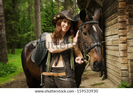 Young cowgirl with brown horse on the ranch