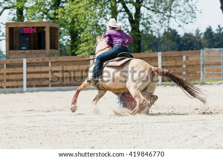 Young cowgirl with hat riding a beautiful paint horse in a barrel racing event at a rodeo in Mitrov, Czech republic - stock photo