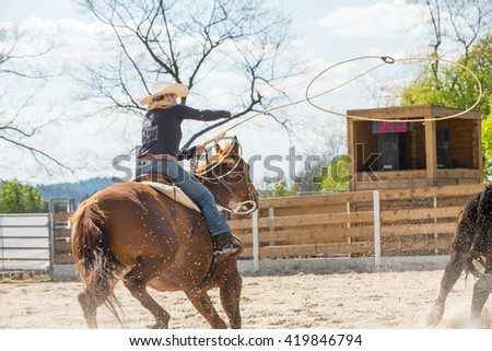 Young cowgirl with hat riding a beautiful paint horse in racing event at a rodeo in Mitrov, Czech republic - stock photo