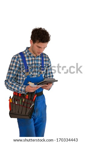 Young craftsman / artisan with a tool belt, money and a calculator  isolated on white background