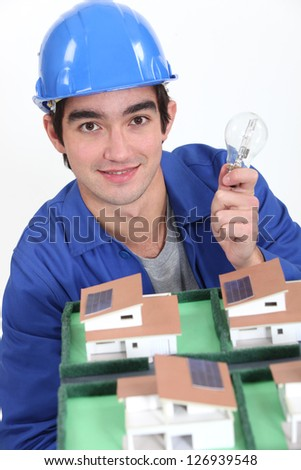 young craftsman holding a bulb and an architectural model of houses - stock photo