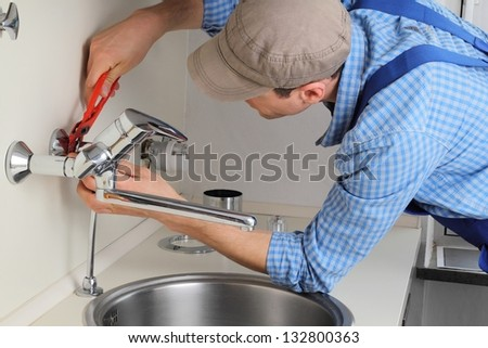 Young craftsman repairing Tap in a kitchen