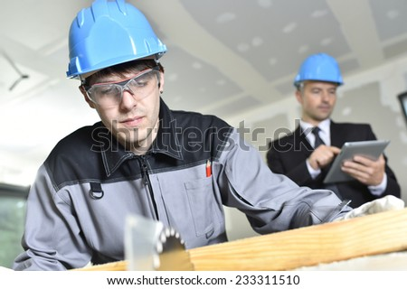 Young craftsman with supervisor in background - stock photo