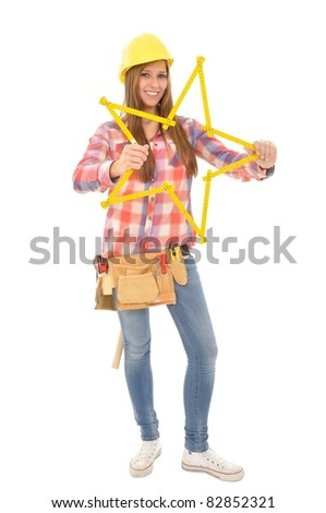 Young craftswoman tinkering a star from a yellow ruler - stock photo
