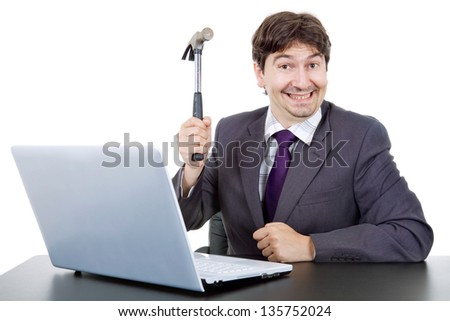 young crazy business man with a hammer smashing a laptop - stock photo