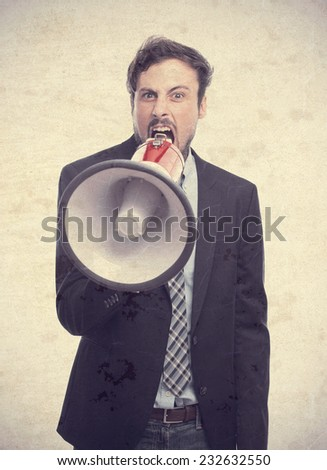 young crazy businessman shouting on megaphone - stock photo