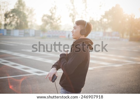 young crazy funny asian man in town outdoor lifestyle listening music with headphones - stock photo