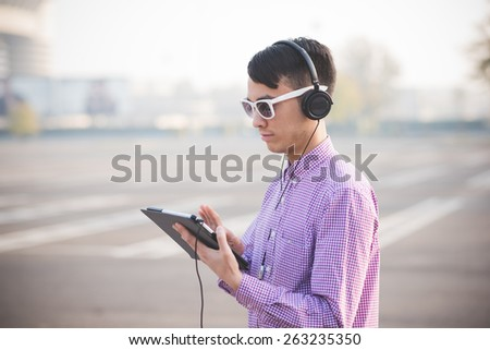 young crazy funny asian man in town outdoor lifestyle listening music with headphones and tablet - stock photo