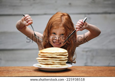 Young crazy girl eating a stack of pancakes.  - stock photo