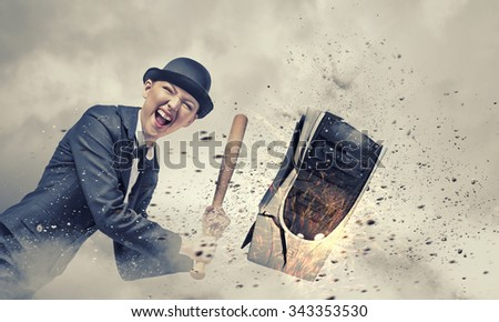 Young crazy woman damaging computer processor with baseball bat - stock photo