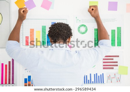 Young creative businessman facing the wall with the charts in the office - stock photo