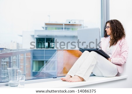 Young creative businesswoman sitting at office window using laptop computer and thinking. - stock photo