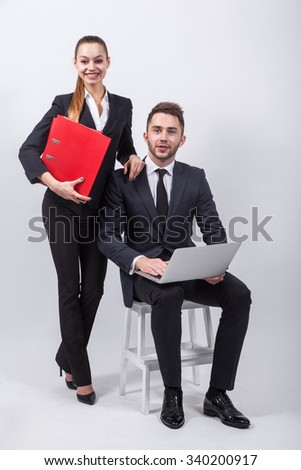 Young creative businesswoman sitting on a chair with a laptop on his knees next to him on a white background is a girl in a classic suit and holding a red office folders.