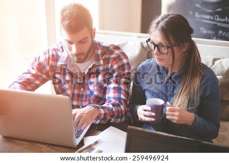 Young Creative Couple Working Together from home - stock photo