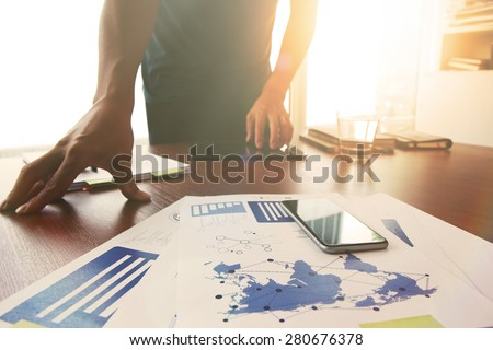 Young creative designer man working at office and social network media and graph chart diagram as concept with overcast exposure effect - stock photo