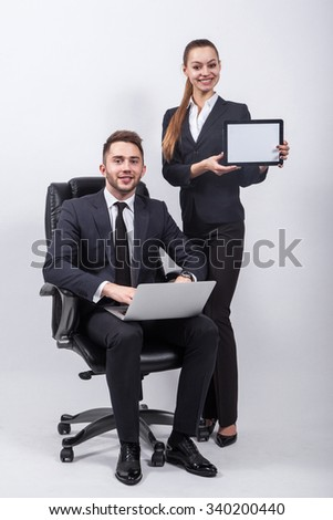 young creative expert sitting in a black leather office chair with a laptop on his knees next to him on a white background is a girl in a classic suit and holding a tablet.