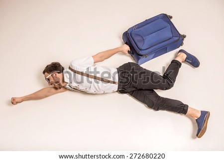 Young creative man is posing with suitcase on grey background. - stock photo
