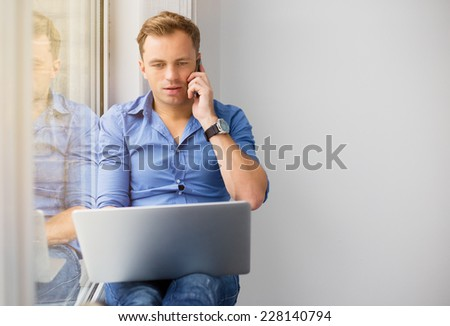 Young creative man working with computer while talking on phone - stock photo