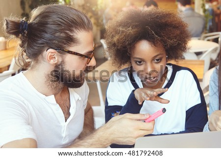 Young creative people of diverse ethnicities brainstorming, discussing strategy of their small company. Stylish African woman explaining her business vision to her bearded colleague with passion