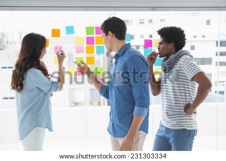 Young creative team brainstorming together in creative office - stock photo