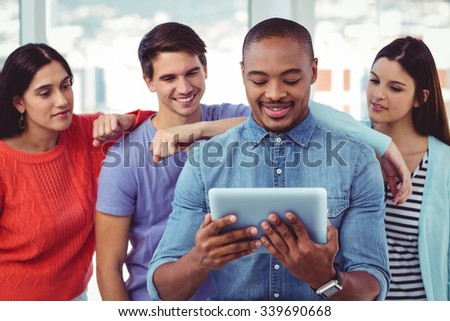 Young creative team looking at tablet in casual office - stock photo