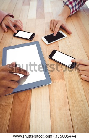 Young creative team using phones and tablet in casual office - stock photo
