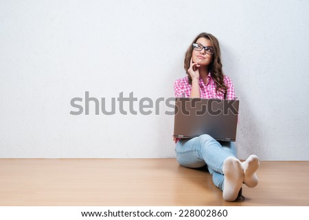 Young creative woman sitting in the floor with laptop./ Casual blogger woman - stock photo