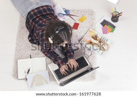Young creative woman stretched in the floor and listening music./ Casual blogger woman working with laptop in her fashion office.  - stock photo