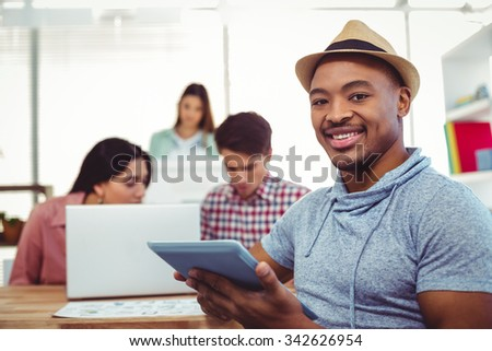 Young creative worker smiling at camera in casual office - stock photo