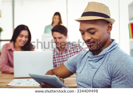 Young creative worker using tablet in casual office - stock photo