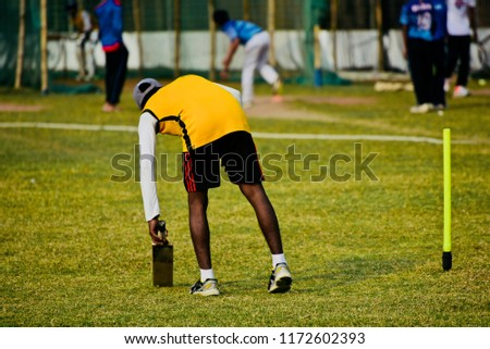 Young cricketer picking up a cricket bat by hand isolated unique photo