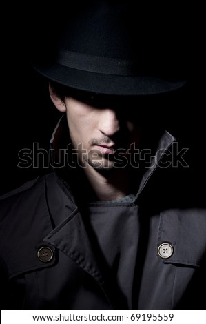 young criminal in shadow, isolated on a black background