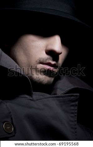 young criminal in shadow, isolated on a black background - stock photo