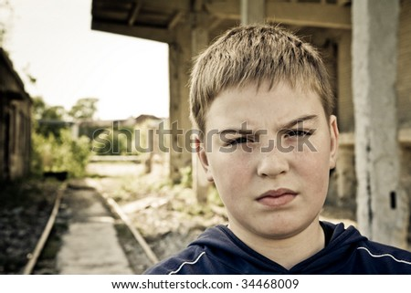 Young criminal on decayed urban backround looking with protest and despair in his eyes - stock photo