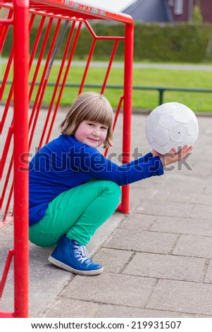 Young crouching girl with ball in red metal goal on schoolyard