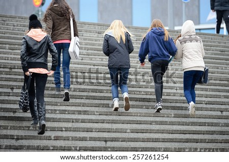 Young crowd walking up the stairs in the rain - stock photo