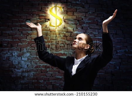 Young crying businesswoman praying on dollar symbol - stock photo