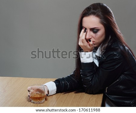 Young crying woman in depression drink drinking alcohol - stock photo