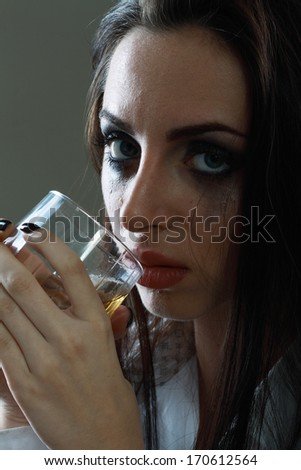 Young crying woman in depression drink drinking alcohol Dark tone image