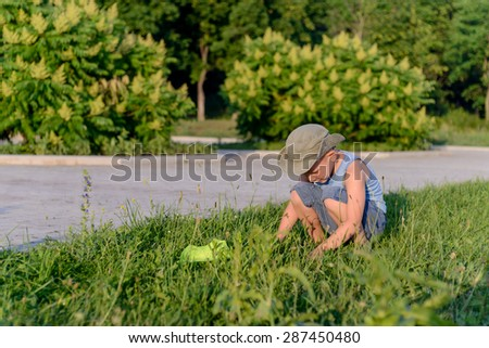 Young Curious Boy Wearing Summer Clothes Crouching in Long Grass on Lawn with Bug Net and Examining Finding on Ground - stock photo
