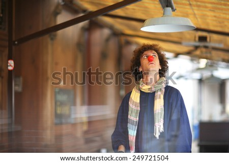 Young curly clown looking at the lamp - stock photo