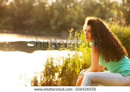 young curly hair woman enjoy in summer sun at lake - stock photo