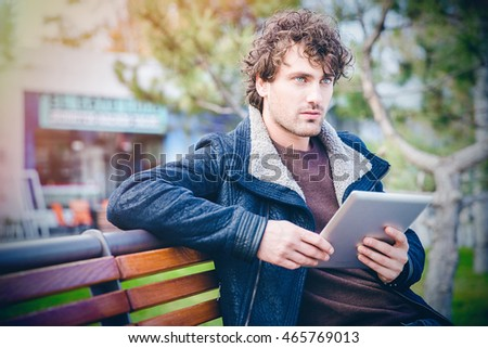 Young curly pensive attractive thoughtful man sitting on wooden bench in the park and holding tablet