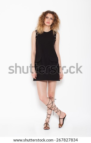 young curly woman posing in modern black dress, on white background