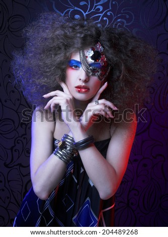 Young curly woman with artistic red and blue visage with silver chain - stock photo