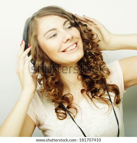 Young curly woman with headphones listening music.Studio shot.
