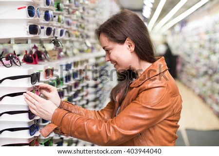 young customer buying sunglasses in optical boutique - stock photo