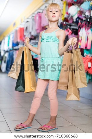 Young customer girl is standing with purchases in the store.