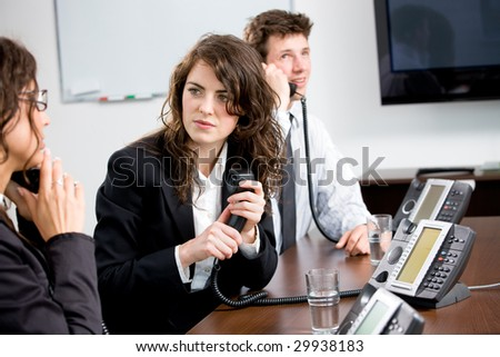 Young customer service operator team working at office, holding phone, calling, giving helpdesk support. - stock photo