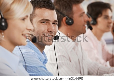 Young customer service operator wearing headset, looking at camera, smiling.